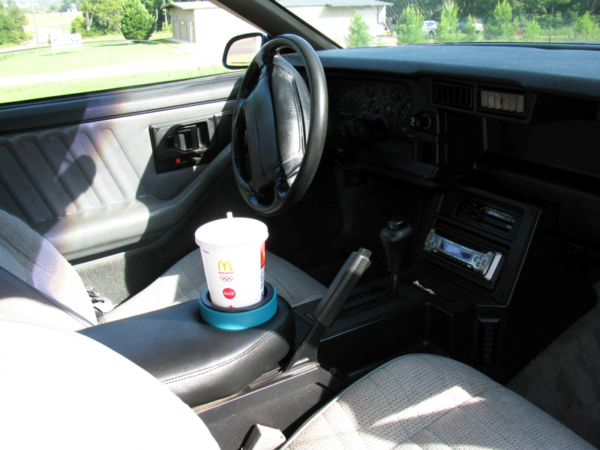 A 1982-1992 Camaro Armrest Pad Cup Holder in a Camaro